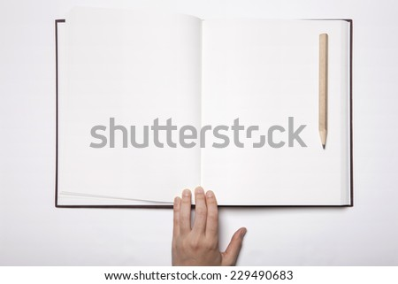 A woman(female) hand hold a empty(blank) book(note, diary) spread(unfold) with wooden pencil isolated white, top view, studio. - stock photo