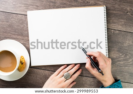 A woman(female) two hands hold a empty(blank) book(note, diary) spread(unfold) sketchbook top view. Designer draws sketches at the table coffee break. Inspiration. Beautiful silver jewelry.  - stock photo