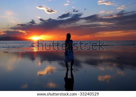 A woman gazing into an amazing sunset - stock photo