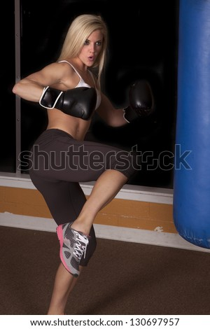 a woman getting ready to kick the bag with her foot. - stock photo