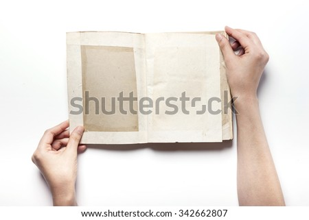 A woman(girl, female) hands hold(write) a empty(blank, vacant, hollow) vintage(old) note(diary, book) spread isolated white at the studio. - stock photo