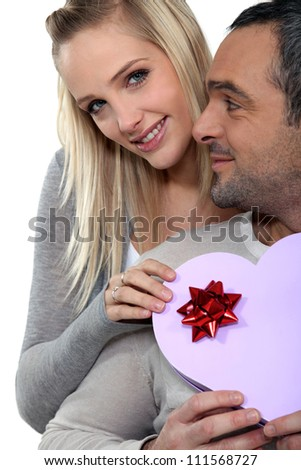 a woman giving a heart shaped box to her husband - stock photo