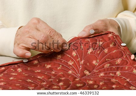 A woman hand stitches the border to finish a quilt. - stock photo