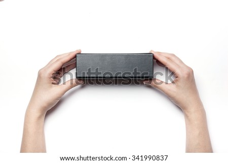 A woman hands hold a empty(blank, vacant, hollow) leather black box(package) for glasses top view isolated white at the studio. - stock photo