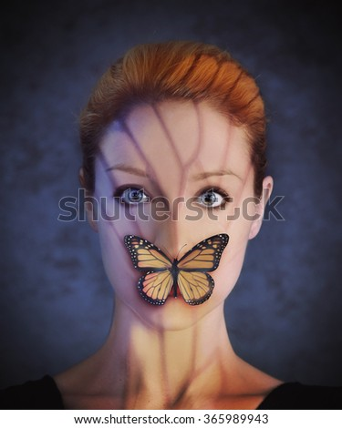 A woman has a yellow monarch butterfly covering her mouth for a silence or communication concept. - stock photo