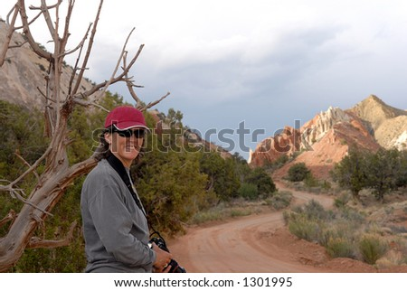 A woman hiker smiles as she rounds a beautiful corner in Southwest Utah's beautiful back-country. - stock photo