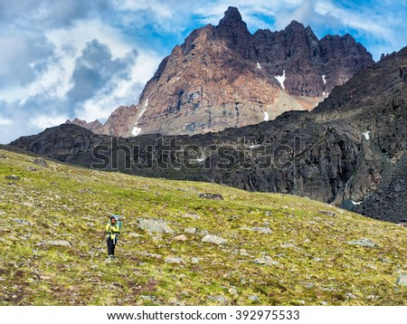 A woman hikes with a backpack on the alpine tundra high in the Alaska Range - stock photo