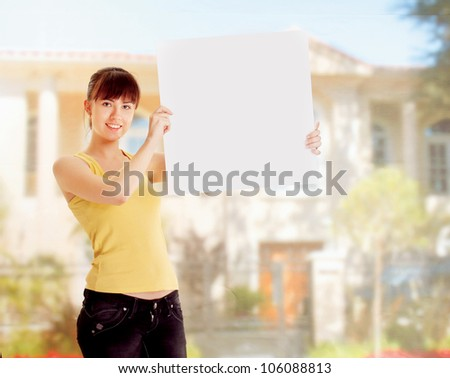 A woman holding a blank outdoors - stock photo