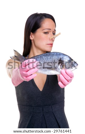 A woman holding a fish at arms length whilst wearing pink rubber gloves and a clothes peg on her nose. Isolated on white background, focus on the fish. - stock photo
