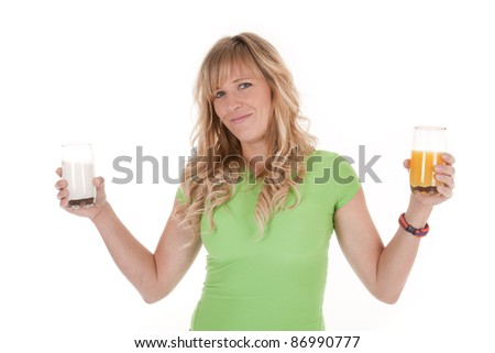 A woman holding a glass of milk and a glass of orange juice with a smile on her face. - stock photo