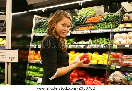 A woman holding a vegetable while grocery shopping - stock photo