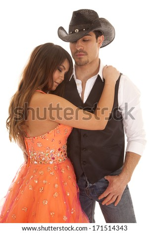 a woman holding on tight to her cowboy. - stock photo