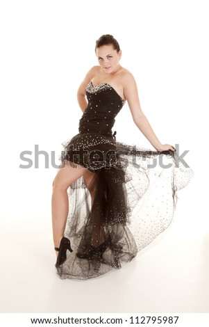 A woman holding on to her dress with a sensual expression on her face. - stock photo
