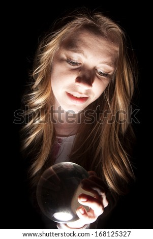 a woman holding on to her glowing crystal ball. - stock photo