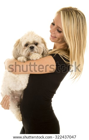 a woman holding on to her puppy with a smile. - stock photo