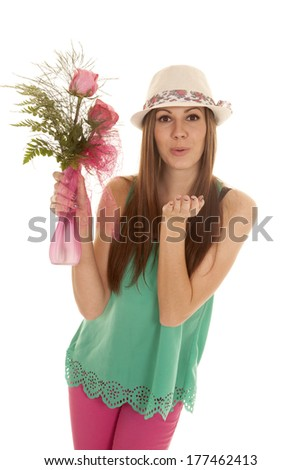 a woman holding on to roses blowing a kiss - stock photo