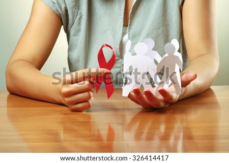 A woman holding paper peolple and an aids red ribbon - stock photo