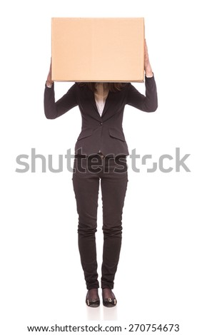 A woman holding up a box in an office setting with other boxes in the background. Isolated on white background. - stock photo