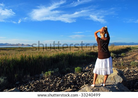 A woman holding up her hair overlooking a field - stock photo