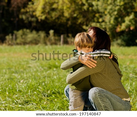 A woman hugging a boy in a field. - stock photo
