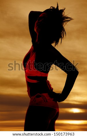 A woman in a bikini in the sunset hand in hair - stock photo