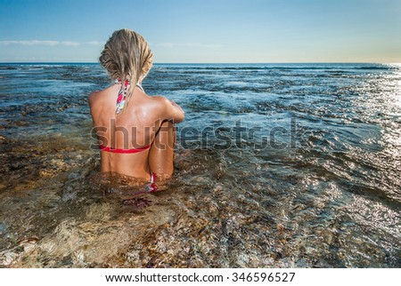 A woman in a bikini sitting in very clear water looking out to a calm sea - stock photo
