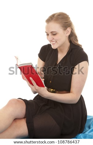 A woman in a black dress is sitting with a smile and reading. - stock photo