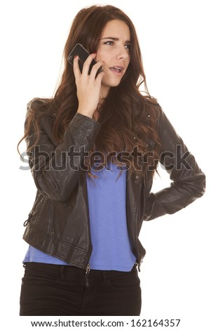 A woman in a black leather jacket is talking on the phone. - stock photo
