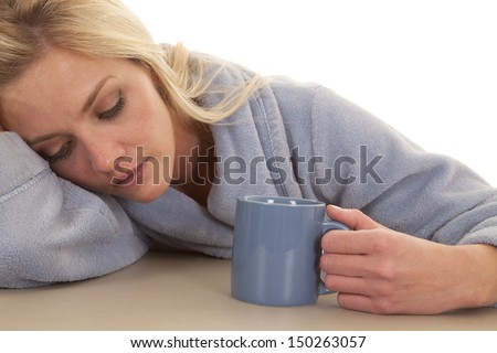 A woman in a blue robe sleepy with a mug. - stock photo