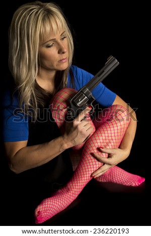A woman in a blue shirt and pink fishnets sitting with a gun in her hand. - stock photo