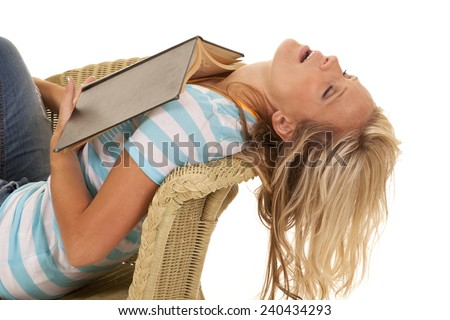A woman in a chair sleeping with a book on her chest. - stock photo