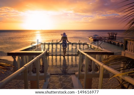 A woman in a hat looking at the romantic Caribbean sunset while standing on the balcony. Roatan Island, Honduras - stock photo