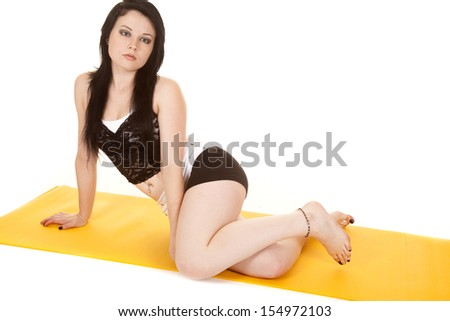 A woman in a lace top is sitting on a yellow mat. - stock photo