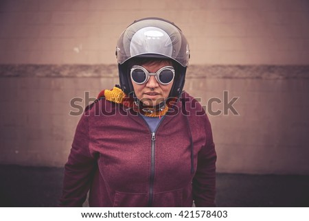 a woman in a motorcycle helmet with steampunk goggles on in front of a wall toned with a retro vintage instagram filter effect app or action  - stock photo