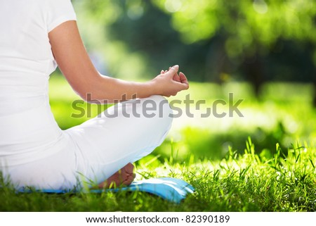 A woman in a park in the lotus position in close-up - stock photo