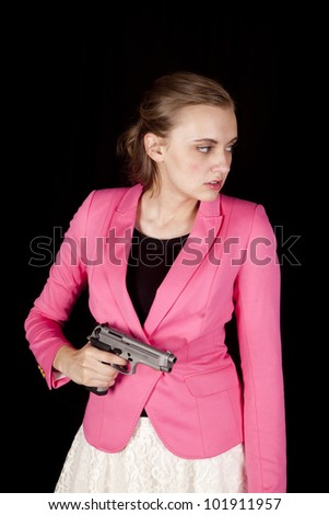 A woman in a pink jacket is holding a gun and looking to the side. - stock photo