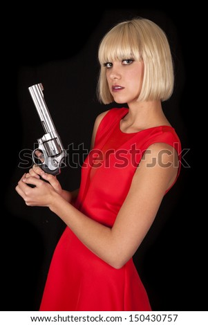 A woman in a red dress holding a gun. - stock photo