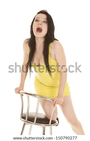 A woman in a short yellow dress mouth open screaming. - stock photo