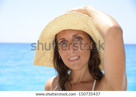 A woman in a straw hat on the sea shore - stock photo