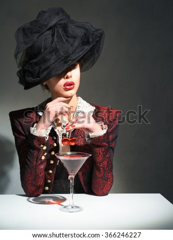 A woman in a vintage hat drinking a martini with a cherry - stock photo