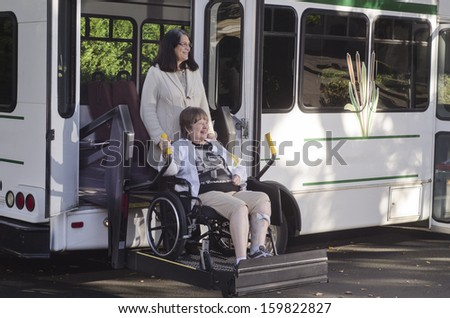 A woman in a wheelchair is helped off a van using a chair lift. - stock photo
