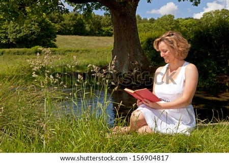 A woman in a white dress sat by a stream reading a book on a bright summers day. - stock photo