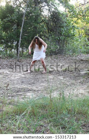 A woman in a white gown, possibly a zombie, wonders in a forest - stock photo