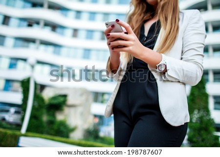 A woman in a white jacket holding a phone in his hand on the street - stock photo