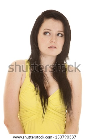 A woman in a yellow dress scared look to side. - stock photo