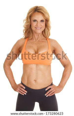 A woman in an orange sports bra with her hands on her hips. - stock photo
