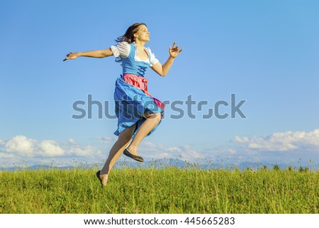 A woman in bavarian traditional dirndl jumping in the nature - stock photo