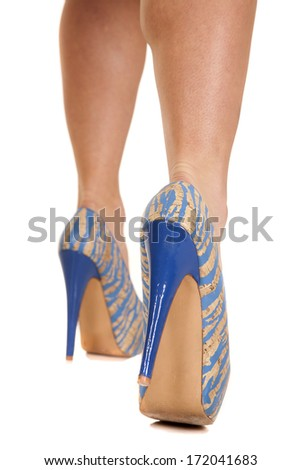 A woman in blue and tan heels legs only. - stock photo
