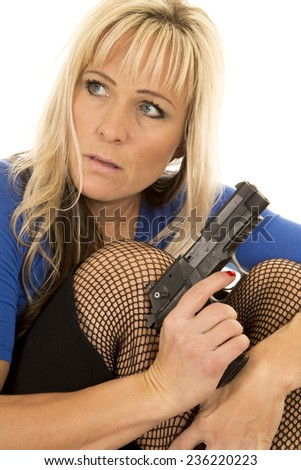A woman in fishnet stockings holding a gun looking to the side. - stock photo