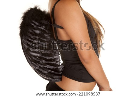 A woman in her angel wings in her black clothes. - stock photo